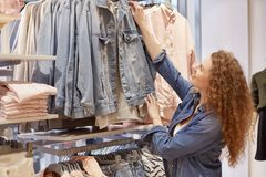 Photo of female shopaholic chooses new denim jacket, likes stylish fashionable clothing, makes shopping in big shopping mall, goin. G to try on new outfit royalty free stock photo