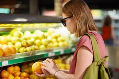 Photo of female teenager stands back, carries rucksack on back, chooses oranges for making fruit salad, wears shades, keeps to hea stock photos
