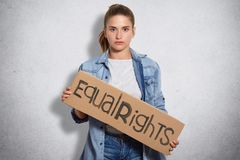 Photo of feminist in denim jacket, holds sign written Equal rights, shows that women have rights and power, isoated over white con. Photo of feminist in denim royalty free stock photography