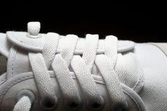 Photo fermée- de l'espadrille blanche sur le fond foncé images stock