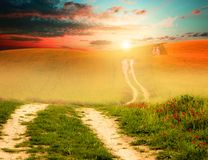 Sunset field and road. Photo of field with fresh green grass, setting sun and road; green, orange and blue colors Royalty Free Stock Photography