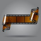 Photo film strip. Curled photo film strip on gray background. Movies concept. Contain the Clipping Path. There is in addition a vector format (EPS 10 Royalty Free Stock Photo