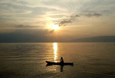 Photo of Fisherman and Sunrise in Lake Toba Stock Photos