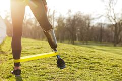 Photo of fit disabled girl in sportswear doing gymnastic and stretching prosthetic leg on grass using rubber band. Photo of fit disabled girl in sportswear stock images