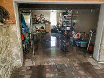 Image of flooded garage after heavy rain. Wet floor and floating thing in house after flood. Photo of flooded garage after heavy rain. Wet floor and floating royalty free stock photo