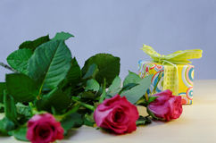 Photo focused on the colorful present surrounded by red roses Stock Images