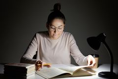 Photo of focused woman has hair knot, has serious clever expression in textbook, sits at desk with lamp, busy with exam preparatio. N, poses indoor. Dark colours royalty free stock photography