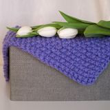 Folded knitted blanket on the gray box stock photo