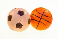 Photo of football and basketball balls on a light background. Photo of toy soccer and basketball balls on a light background royalty free stock images