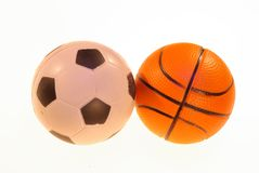 Photo of football and basketball balls on a light background. Photo of toy soccer and basketball balls on a light background stock photography