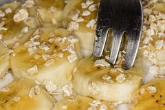 Fork jabbing banana slices with oats and honey stock photo