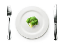Photo of the fork and knife with white plate and broccoli on whi Stock Photography