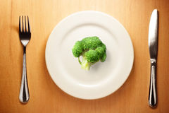 Photo of the fork and knife with white plate and broccoli on woo Royalty Free Stock Photos
