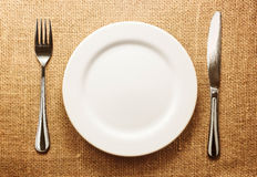 Photo of the fork and knife with white plate on sa Royalty Free Stock Images