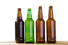 Photo of four different full beer bottles with no labels. Separate clipping path for each bottle included. Four 4 separate photos. Merged together. Beer bottles royalty free stock photos