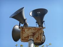 Four grey metal alarm loudspeakers. Photo of four grey metal alarm loudspeakers taken on sunny day, bright blue sky in background stock images