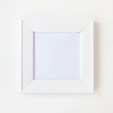 Photo frame. Square simple blank white photo frame on wall royalty free stock photo