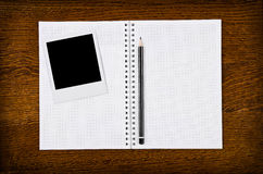 Photo frame on blank notebook with pencil. Classic instant photo frame on blank notebook with pencil Stock Photos