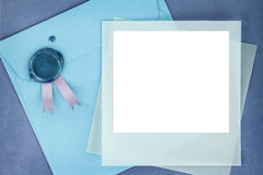 Photo frame on blue envelope. Photo frame and paper envelope with sealing wax stamp stock photo