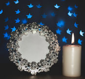 Photo frame with blur blue stars and burning candle. Abstract - photo frame with blur blue stars and burning candle on black background Royalty Free Stock Images