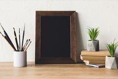 Photo frame and book on tabletop. Close up view of photo frame, plants in flowerpots, paintbrushes and books on wooden tabletop stock photos
