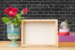 Photo frame, books and flowers on the wooden table with blue woo Stock Photos