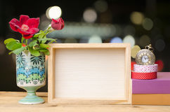 Photo frame with books and flowers on the wooden table on bokeh background Royalty Free Stock Photography