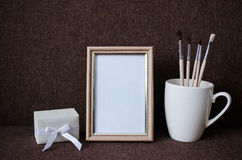 Photo frame, brush in a cup and a box Royalty Free Stock Image