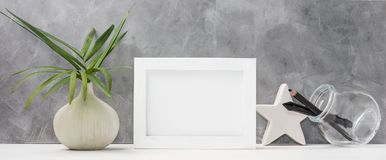 Photo frame close up mock up with palm leaves in vase, ceramic star, pen and pencil in mason jar on shelf. Scandinavian style. Text space Royalty Free Stock Photography