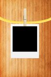 Photo frame with clothespin over wooden. Background Stock Photography