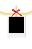 Photo frame with clothespin and red bow isolated on white Royalty Free Stock Photo