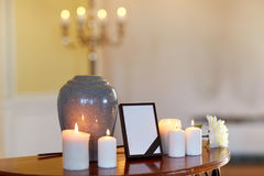 Photo frame, cremation urn and candles in church. Funeral and mourning concept - photo frame with black ribbon, cremation urn and burning candles on table in stock photos