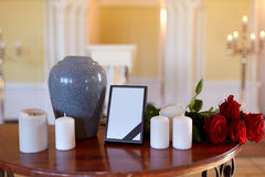 Photo frame, cremation urn and candles in church Royalty Free Stock Photos