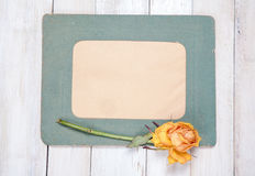 Photo frame with dry rose. Retro photo frame with dry rose on white wooden background Stock Photos