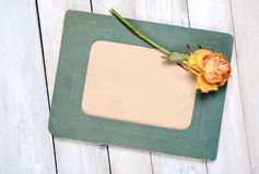 Photo frame with dry rose. Retro photo frame with dry rose on white wooden background Stock Photo
