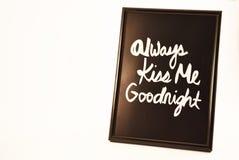 Photo frame always kiss me goodnight. Black photo frame containing white text always kiss me goodnight on white background Stock Photos