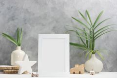 Photo frame mock up with plants in vase, ceramic decor on shelf. Scandinavian style. Text space royalty free stock image