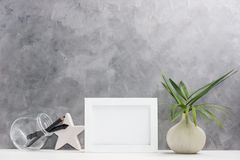 Photo frame mock up with plants in vase, ceramic star, pen and pencil in mason jar on shelf. Scandinavian style. Text space Stock Photography