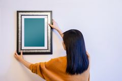 Photo Frame Mockup with Clipping Path. Woman Decorating a New Ho. Use by Hanging the Blank Picture Frame on the Wall stock photography