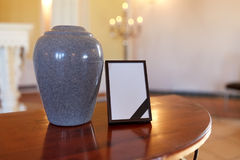 Photo frame with mourning ribbon and cremation urn Stock Photos