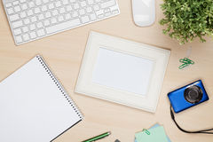 Photo frame on office table with notepad, computer and camera Royalty Free Stock Image