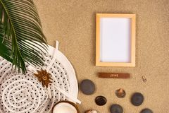 Photo frame, palm leaf and hat on sand background. Top view royalty free stock photo