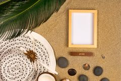 Photo frame, palm leaf and hat on sand background. Top view royalty free stock photography