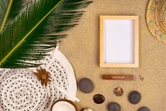 Photo frame, palm leaf and hat on sand background. Top view royalty free stock photos