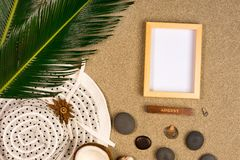 Photo frame, palm leaf and hat on sand background. Top view royalty free stock image