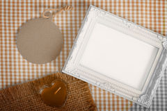 Photo frame and paper tag and heart candle in glass over fabric Stock Photo