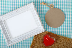 Photo frame and paper tag and red heart sign candle in glass ove Royalty Free Stock Photo
