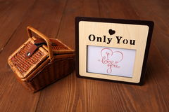 Photo frame and picnic basket. Photo frame and picnic basket on a wooden background Stock Photography