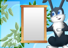 Photo frame with rabbit. Background with photo frame and a smiling gray rabbit. Sky, clouds, green bushes Stock Photography