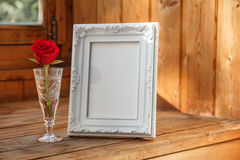 Photo frame and a red rose. White photo frame and red flower Royalty Free Stock Image